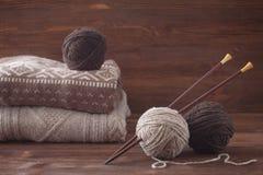 花呢与木编织针的毛纱 被编织的毛线衣 免版税库存照片