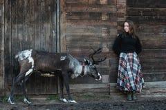 花呢格子裙子的一个年轻欧洲女孩在驯鹿旁边站立在木墙壁附近 库存图片