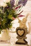 花和一个天使在白色桌上 库存照片