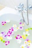 花和矿泉水在浴缸 免版税库存图片