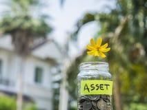 花和硬币在玻璃瓶子有标记的 免版税库存图片