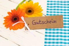 花和礼品券与德国词、Gutschein、手段证件或者优惠券为父亲` s天或生日 免版税库存照片