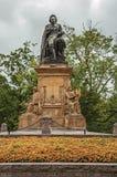 花和纪念碑与约斯特・范・登・冯德尔雕象在阿姆斯特丹停放 免版税库存图片
