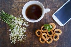 花和茶花束在一张木桌上的与有黑屏的电话 免版税图库摄影