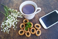 花和茶花束在一张木桌上的与有黑屏的电话 免版税库存图片