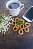花和茶花束在一张木桌上的与有黑屏的电话 免版税库存照片
