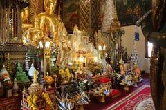 花和金黄菩萨雕象奉献物装饰一个寺庙(泰国) 免版税库存图片