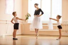年轻给花和面纱的男孩和女孩更老的学生,当她跳舞en pointe时 免版税图库摄影