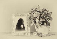花和维多利亚女王时代的框架夏天花束与少妇葡萄酒画象在木桌上 黑白样式imag 库存图片