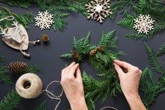 花圈、装饰、麻线、枝杈和雪花圣诞节车间  妇女准备一个花圈 名列前茅v 免版税库存图片