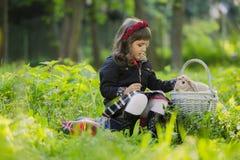 花圈的一个小女孩观察在篮子的一只兔子在日落在公园 库存图片