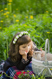 花圈的一个小女孩观察在篮子的一只兔子在日落在公园 免版税库存照片