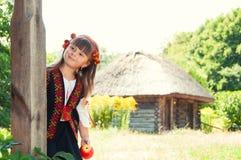 花圈的女孩和与乌克兰装饰品的一套衣服在有木房子的乡下 免版税库存图片