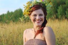 花圈的美丽的妇女在干燥领域微笑对夏天 免版税库存照片