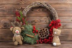 花圈 圣诞节在黑暗的木背景的冬天框架 红色元素钩编编织物卡拉服特玩具猫和鹿 免版税库存图片