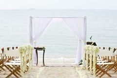 花在海滩婚礼地点的装饰椅子 免版税图库摄影