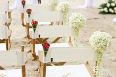 花在海滩婚礼地点的装饰椅子 库存图片