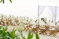 花在海滩婚礼地点的装饰椅子 免版税库存图片