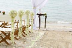 花在海滩婚礼地点的装饰椅子 库存照片