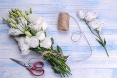 花在蓝色木背景的南北美洲香草和丝带白色花束与剪刀的 免版税库存照片