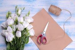 花在蓝色木背景的南北美洲香草和绳索白色花束与包装纸剪刀的 免版税图库摄影