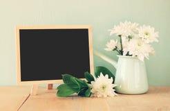 花夏天花束在木桌和黑板上的有文本的室的有薄荷的背景 葡萄酒被过滤的图象 免版税库存图片