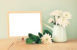 花夏天花束在木桌和黑板上的有文本的室的有薄荷的背景 葡萄酒被过滤的图象 免版税库存照片