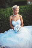 花她的婚礼礼服和花束的年轻新娘  免版税库存图片