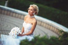 花她的婚礼礼服和花束的年轻新娘  库存图片