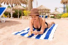 花姑娘在沙子的毛巾晒日光浴在海滩并且保护她的有sunblock的手 库存图片