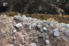 花岗岩石头,沙子和地球,在泥煤本地准备的提取时路的建筑的开掘了 免版税库存图片