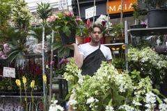花店在哥伦比亚路花市场上转动他的销售发出答答声,当拿着一朵唯一花时 库存图片