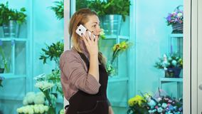 花店的店主谈话在看花的陈列室电话和步行 股票视频