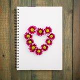 花心脏sumbol在木背景隔绝的笔记本的 平的位置,顶视图 库存照片