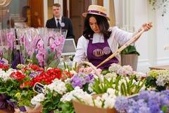 花推销员花束为在购物中心` Petrovsky段落`的销售做准备在莫斯科 免版税库存照片