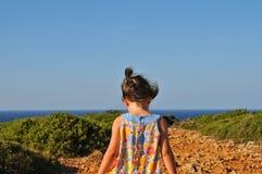 花服的小女孩走到海岸的 库存图片