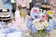花束和礼物在表上在婴儿送礼会 免版税库存图片