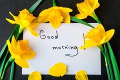 黄水仙花束在卡片附近的与在黑背景的早晨好 顶视图 复制空间 母亲节或妇女天 问候 免版税库存照片