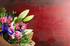 花束开花与玫瑰、虹膜和百合 免版税图库摄影