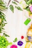 花束用夏天花和植物的辅助部件做在白色木背景,顶视图 免版税库存照片