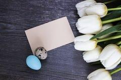花束白色郁金香开花与与在木的复活节彩蛋egs 图库摄影