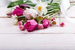 花束第一朵春天花、桃红色、紫色郁金香、黄水仙和雏菊在白色木背景 库存照片