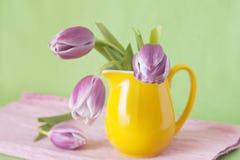 花束精美水罐紫色郁金香黄色 库存照片