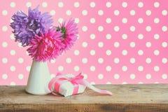 花束翠菊开花,有丝绸丝带的礼物盒 免版税库存照片