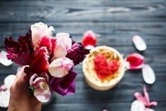 花束郁金香和红色木心脏在黑暗的桌上的箱子在 免版税库存照片