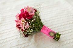 3花束重点前景婚礼 新娘` s花束 红色和桃红色花花束,与桃红色丝带和古董别针谎言 免版税库存照片