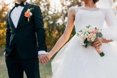 3花束重点前景婚礼 有一件白色礼服的被弄脏的无尾礼服的新娘和新郎握手 在花的软的焦点 免版税图库摄影