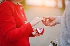 花束金刚石订婚结婚提议环形玫瑰 供以人员举行定婚戒指在红色箱子在他的ha 免版税库存图片
