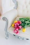 花束黄色和玫瑰色郁金香葡萄酒椅子在绝尘室 图库摄影