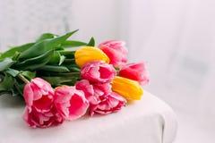 花束黄色和玫瑰色郁金香葡萄酒椅子在绝尘室 免版税库存照片